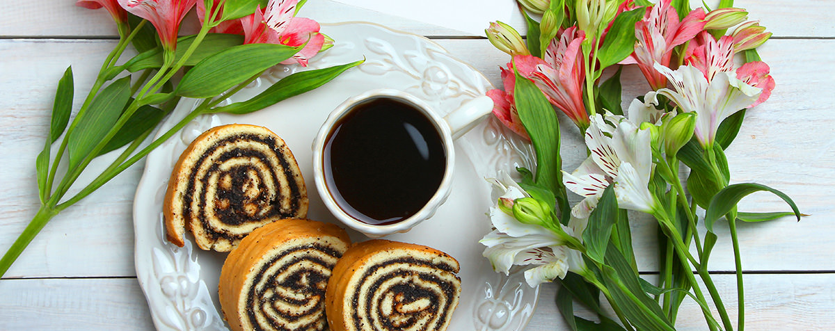 Black coffee and cinnamon rolls plate on a wooden background